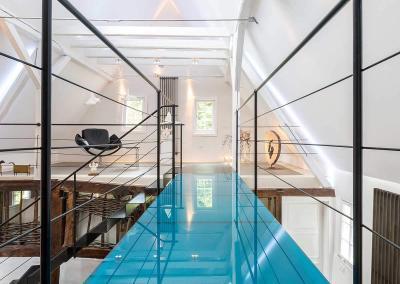 Eine blaue Glasbrücke verbindet die Galerien der zweiten Ebene im Veranstaltungsraum Erlebnisraum.