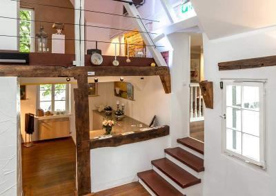 Einganstreppe des Erlebnisraums mit Blick auf urige Holzbalken und seine zwei modern gestaltete Ebenen.