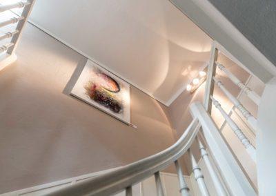 Weißes Geländer und Kunstwerk im Treppenhaus der Buchmühle Bergisch Gladbach