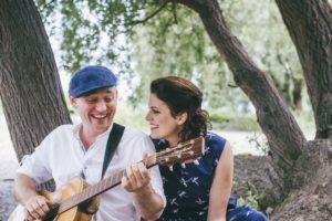 Florian Walther und Anne Gladbach lächelnd mit Gitarre.
