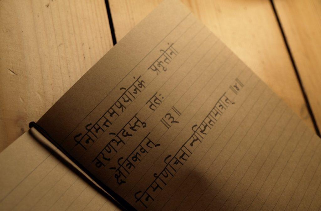 Sutren in Sanskrit auf Linienpapier