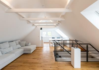 Langes Sofa, Arbeitsplatz und Treppengelände im Dachgeschoss der Buchmühle Bergisch Gladbach