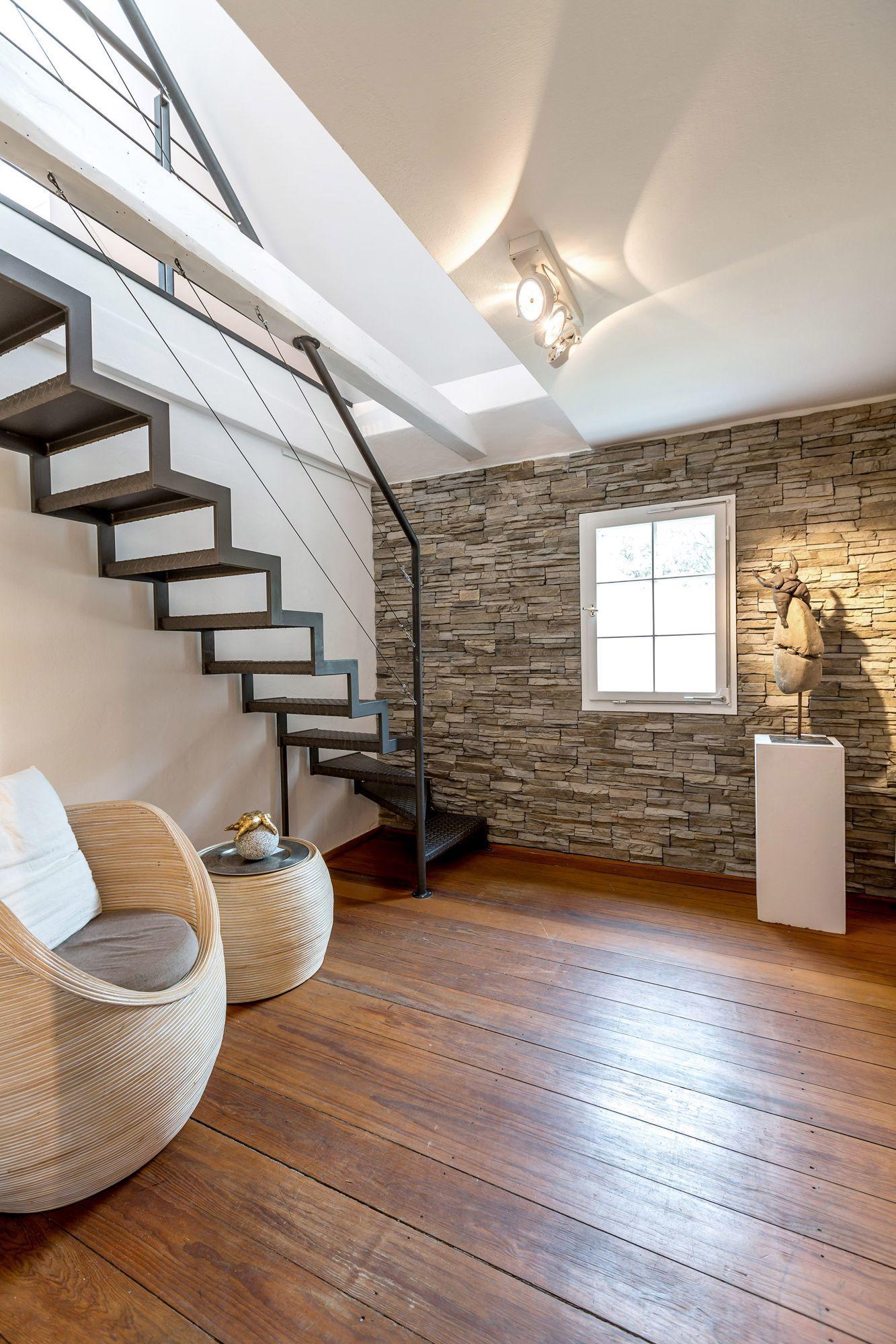 Vorraum mit Sitzecke, Steinwand und Stahltreppe zum Dachboden der Buchmühle Bergisch Gladbach.