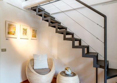 Ein heller Sessel mit Tischchen unter der Stahltreppe zum Dachgeschoss der Buchmühle